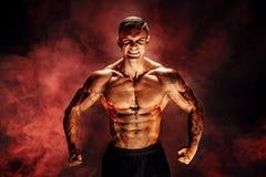 bodybuilder θέτοντας Η ικανότητα διάστισε το muscled άτομο στο κόκκινο υπόβαθρο καπνού Στοκ Φωτογραφία