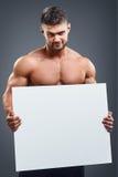 Bodybuilder με την κενή άσπρη αφίσα Στοκ Φωτογραφία
