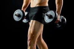 Bodybuilder με τους αλτήρες στο Μαύρο στοκ εικόνες