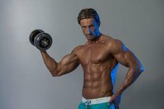 Bodybuilder που ασκεί τους δικέφαλους μυς με τους αλτήρες στο γκρίζο υπόβαθρο Στοκ Φωτογραφίες