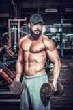 Bodybuilder που κάνει τις ασκήσεις με τους αλτήρες Στοκ Εικόνες