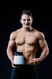 Bodybuilder που κρατά μια μαύρη πλαστική πρωτεΐνη ορρού γάλακτος ετικετών βάζων κενή άσπρη και που δείχνει την με το χέρι του που στοκ φωτογραφία με δικαίωμα ελεύθερης χρήσης