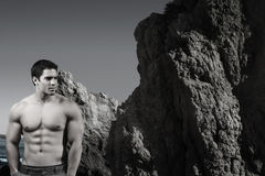 Bodybuilder. Stylized portrait of young male shirtless bodybuilder with mountain, ocean, and sky behind him Royalty Free Stock Image