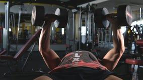 Πολύ ο αθλητικός τύπος δύναμης bodybuilder, εκτελεί την άσκηση με τους αλτήρες, στη σκοτεινή γυμναστική φιλμ μικρού μήκους