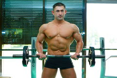 Bodybuilder. The young sports guy trains in a gym lifting a bar Royalty Free Stock Photos
