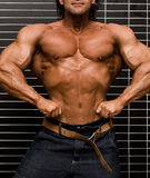 Bodybuilder. In front of wall stock image
