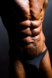 Bodybuilder abdomen. Closeup of bodybuilder abdomen on black background Royalty Free Stock Images