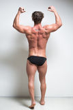 Bodybuilder against a white wall. is back. Sexy bodybuilder against a white wall. is back.  full height Stock Photos