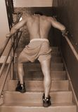 Bodybuilder in assending the stairs Stock Photos