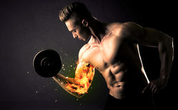 Bodybuilder athlete lifting weight with fire explode arm concept Royalty Free Stock Image