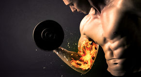 Bodybuilder athlete lifting weight with fire explode arm concept Royalty Free Stock Images