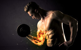 Bodybuilder athlete lifting weight with fire explode arm concept Royalty Free Stock Photography