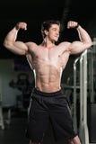 Bodybuilder-Ausführungsfront double biceps pose in-Turnhalle stockfoto