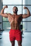 Bodybuilder-Ausführungsfront double biceps pose in-Turnhalle stockbilder
