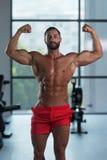Bodybuilder-Ausführungsfront double biceps pose in-Turnhalle lizenzfreie stockbilder
