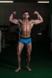 Bodybuilder Ausführungsfront double biceps poses lizenzfreie stockbilder