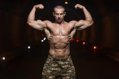 Bodybuilder-Ausführungsfront double biceps poses in-Tunnel lizenzfreies stockbild