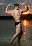 Bodybuilder avec un coucher du soleil photographie stock libre de droits