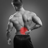 Bodybuilder Back pain. Muscular man with back pain over gray background. Concept with highlighted glowing red spot stock image