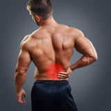 Bodybuilder Back pain. Muscular man with back pain over gray background. Concept with highlighted glowing red spot stock photos