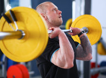 Bodybuilder with barbell in gym Stock Image