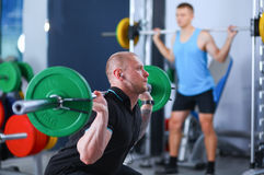 Bodybuilder with barbell in gym Stock Photos