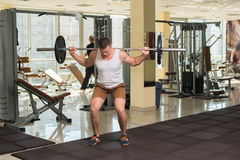 Bodybuilder with barbell in gym. Royalty Free Stock Images