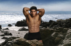 Bodybuilder on Beach. Bodybuilder flexing muscles on the beach with blue sky and ocean Stock Photography