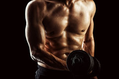Bodybuilder with beads of sweat training in gym. Stock Images