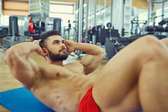 Bodybuilder with a beard does abs exercise on the floor in the g. Ym Royalty Free Stock Image