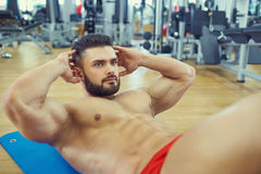 Bodybuilder with a beard does abs exercise on the floor in the g. Ym Stock Images