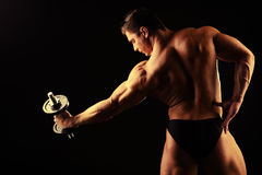 Bodybuilder. Beautiful muscular man bodybuilder posing back over dark background Stock Images