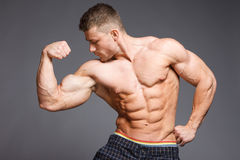 Bodybuilder. The beautiful and strong young guy Royalty Free Stock Photography