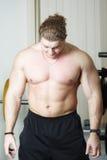 Bodybuilder bending head Stock Photography