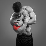 Bodybuilder Biceps pain. Muscular shirtless man with biceps pain over gray background. Concept with highlighted glowing red spot royalty free stock image