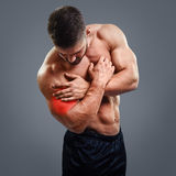 Bodybuilder Biceps pain. Muscular shirtless man with biceps pain over gray background. Concept with highlighted glowing red spot stock photography