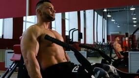 Bodybuilder bildet die Beine, mittleren Plan aus Bemannen Sie das Handeln von Übung mit Gewichthebenmaschine in der Eignungsmitte stock footage