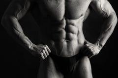 Bodybuilder on black background stock images