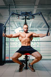 Bodybuilder building arm muscles on a gym background. A shirtless athlete with big hand muscles. Hard workout concept. Royalty Free Stock Photos