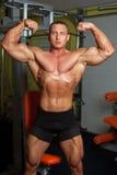 Bodybuilder che dimostra posa nel randello di forma fisica Immagine Stock Libera da Diritti