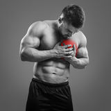 Bodybuilder Chest pain. Muscular shirtless man with chest pain over gray background. Concept with highlighted glowing red spot stock image