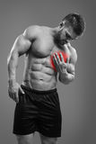 Bodybuilder Chest pain. Muscular shirtless man with chest pain over gray background. Concept with highlighted glowing red spot royalty free stock photos