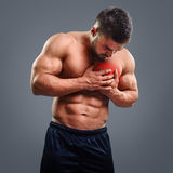 Bodybuilder Chest pain. Muscular shirtless man with chest pain over gray background. Concept with highlighted glowing red spot stock photo