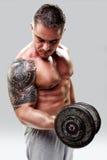 Bodybuilder con i pesi di sollevamento del tatuaggio, primo piano Fotografie Stock