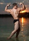 Bodybuilder con una puesta del sol Fotografía de archivo libre de regalías