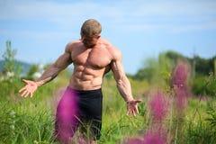 Bodybuilder convenable de torse nu de jeunes démontrant dehors des muscles Images libres de droits