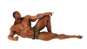 Bodybuilder d'africain noir se trouvant sur la terre Image stock
