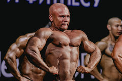 Bodybuilder d'athlète dans une pose faisant face en avant, tendant le coffre et la presse Photographie stock