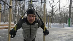 Bodybuilder d'homme faisant l'exercice accroupi sur l'au sol de sports en parc d'hiver photographie stock libre de droits