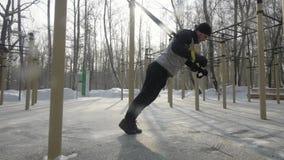 Bodybuilder d'homme faisant l'exercice accroupi sur l'au sol de sports en parc d'hiver images stock